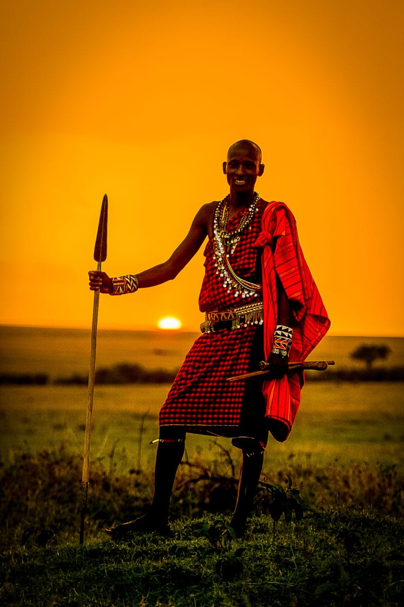 native with red garment against orange sunset sky